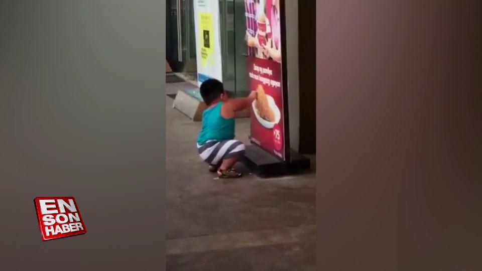 Reklam afişindeki tavukları yemeğe çalışan çocuk